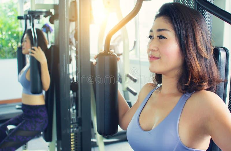 一名亚裔妇女做着在健身房的锻炼 免版税图库摄影