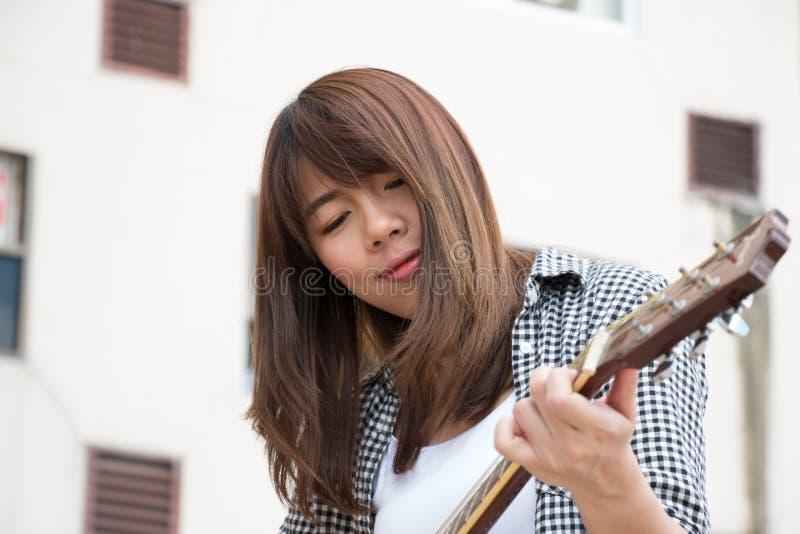 一名亚裔妇女弹吉他 图库摄影
