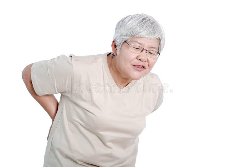 一名亚裔年长妇女表达背部疼痛的行动和隔绝在白色背景 免版税库存照片