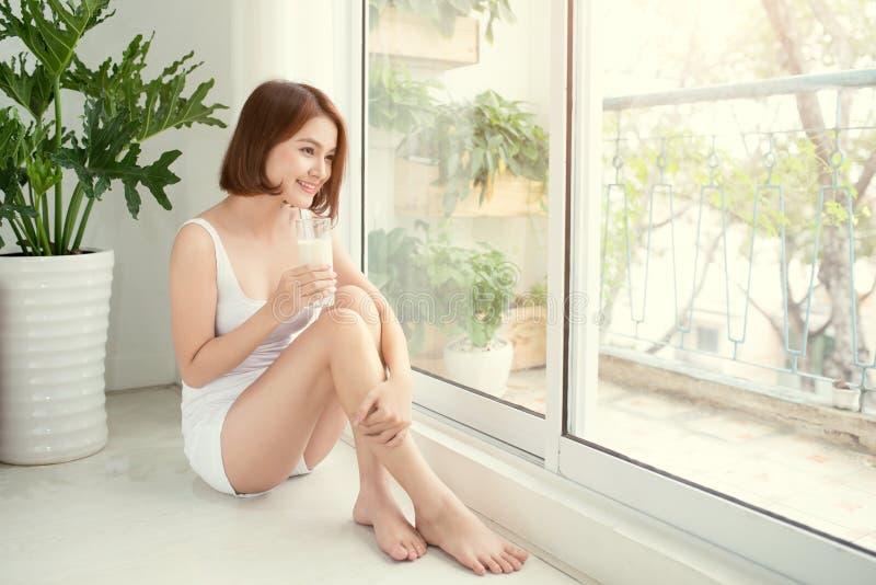 一名俏丽的妇女的画象对负玻璃用牛奶 健康生活方式、素食饮食和膳食 饮料牛奶 医疗保健和好漂亮的东西或人 免版税库存照片