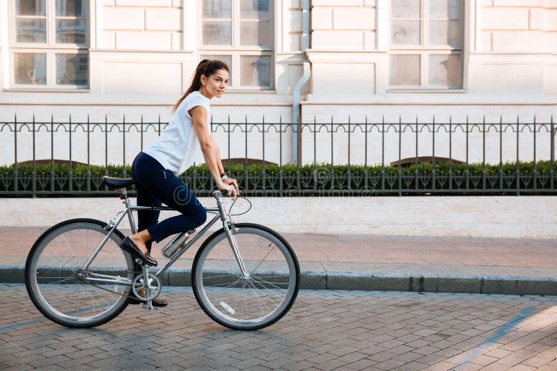 一名俏丽的妇女的画象自行车的在城市 库存图片