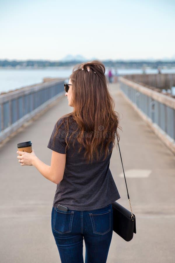 一名俏丽的年轻深色的妇女佩带的太阳镜用在享受海景的海边木板走道的一份咖啡 免版税库存照片