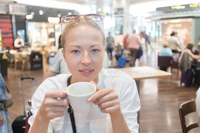 一名偶然年轻白肤金发的妇女的画象饮用一杯咖啡,坐在咖啡馆户内机场,驻地,食物 库存照片