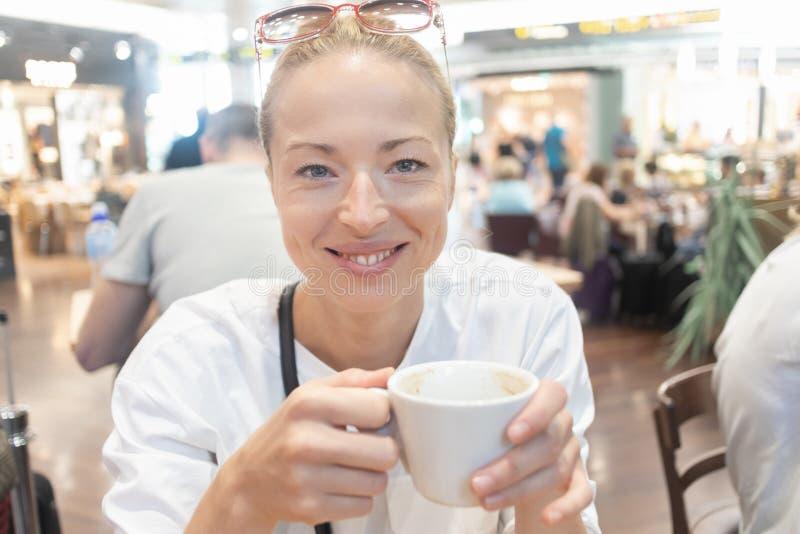 一名偶然年轻白肤金发的妇女的画象饮用一杯咖啡,坐在咖啡馆户内机场,驻地,食物 库存图片