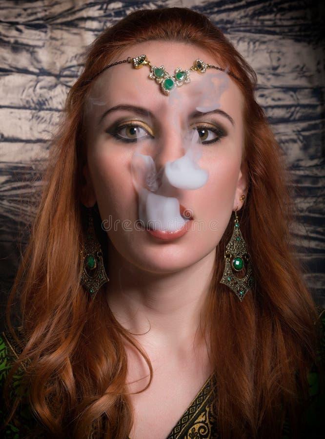一名典雅的年轻红头发人妇女的特写镜头画象,有东方构成和披肩的在她的顶头明亮的红色嘴唇 免版税图库摄影