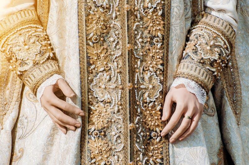 一名历史皇家妇女的衣裳有淡色口气的,有一个圆环的手与宝石 库存照片