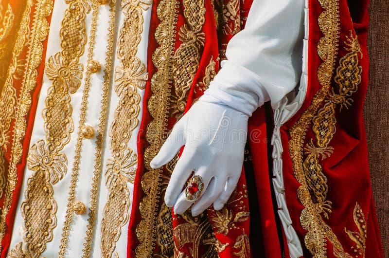 一名历史皇家妇女的衣裳有红色元素、一只手在白色手套和一个圆环的与宝石 免版税库存图片