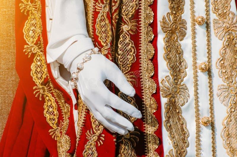 一名历史皇家妇女,在白色手套的一只手的衣裳有红色元素的 库存照片