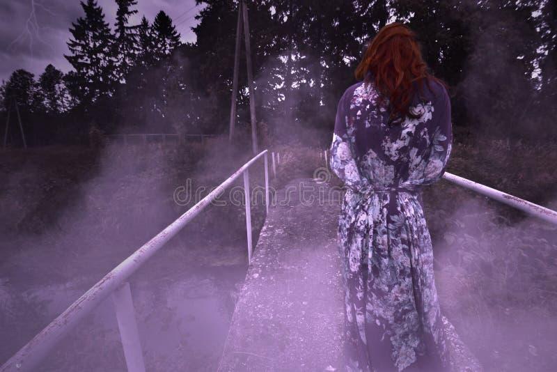 一名可怕的阴险妇女在桥梁站立在雾的晚上 库存图片