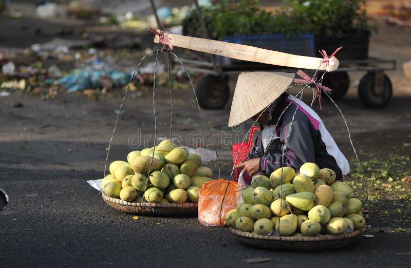 一名可怜的妇女在繁忙的市场上在越南 免版税库存照片