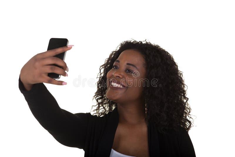 一名可爱的妇女在她的佩带耳朵的二十内发芽看她的电话 库存图片