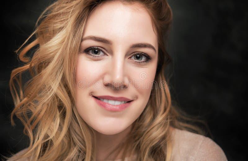 一名可爱的年轻白肤金发的妇女的画象黑背景的 免版税库存图片