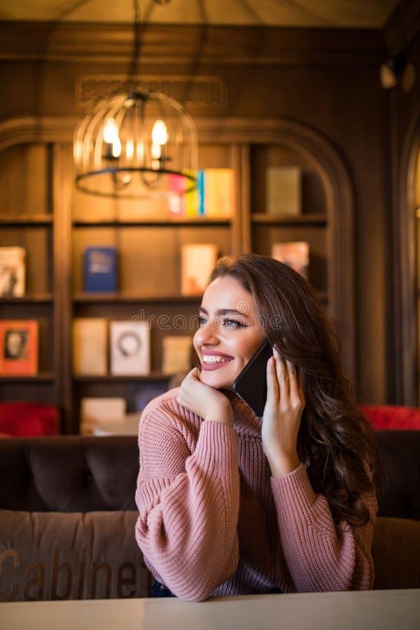 一名可爱的现代妇女与客户通电话 免版税图库摄影