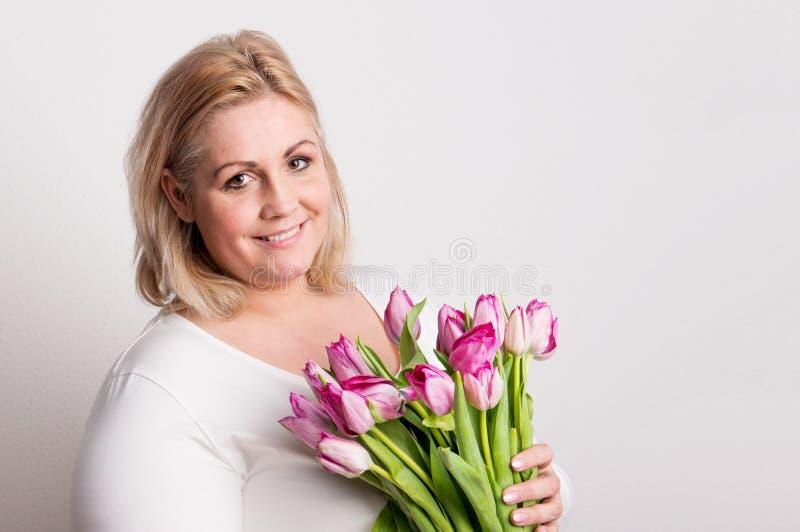 一名可爱的超重妇女的画象有郁金香的在白色背景的演播室 免版税库存照片