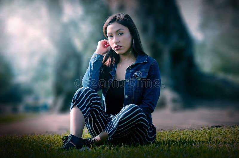 一名可爱,年轻和可爱的深色的妇女的画象坐草坪 免版税库存照片