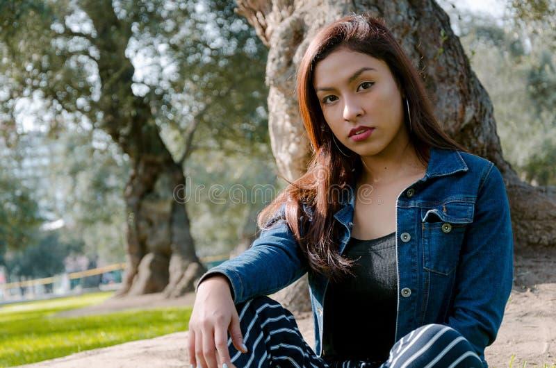 一名可爱,年轻和可爱的深色的妇女的画象坐草坪 图库摄影