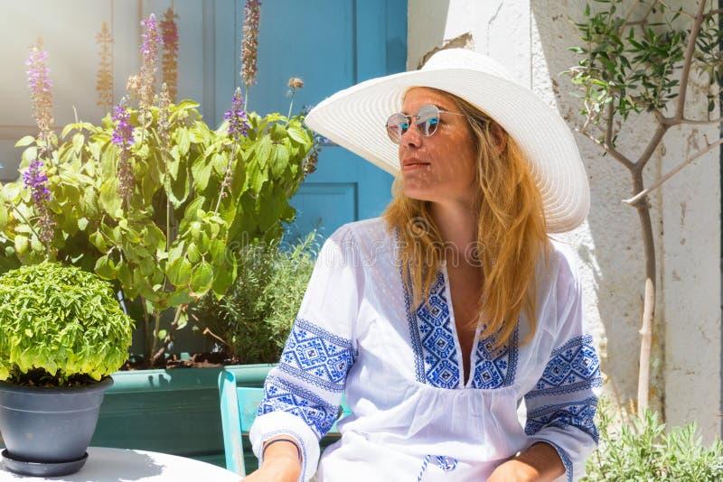 一名可爱,白肤金发的旅行家妇女的画象在希腊海岛上的 库存照片