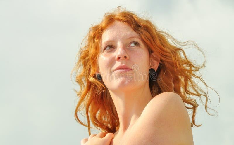 一名周道的年轻红头发人渴望的卷曲妇女的美丽的肉欲的画象在度假由海的有拷贝空间的 免版税图库摄影
