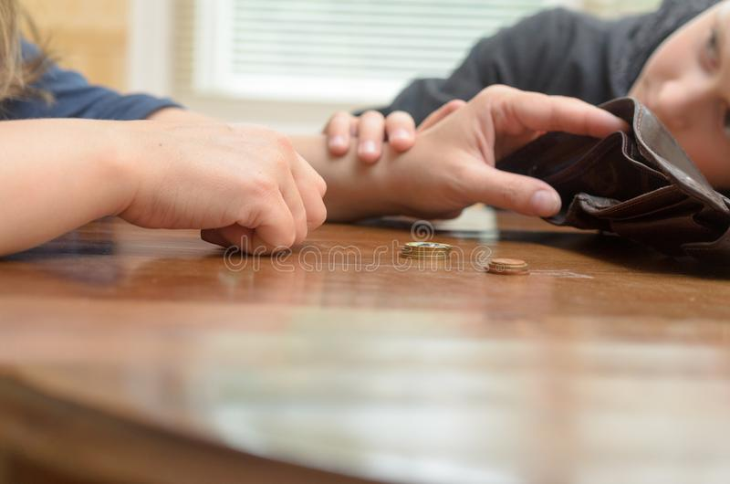 一名哀伤的妇女在桌上认为最后硬币 空的钱包-男孩儿子镇定母亲 库存图片