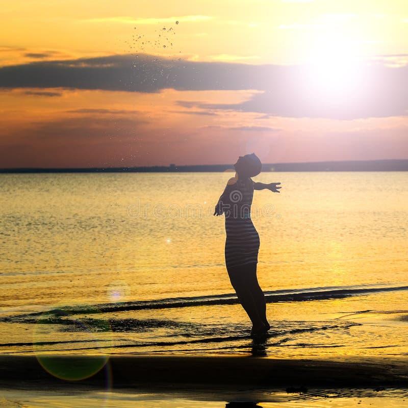 一名坚强的确信的对日落的妇女开放胳膊 库存照片
