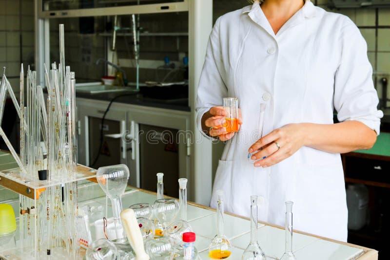 一名女性实验员,医生,化学家,与烧瓶,试管一起使用,做解答,医学,混合成份 图库摄影