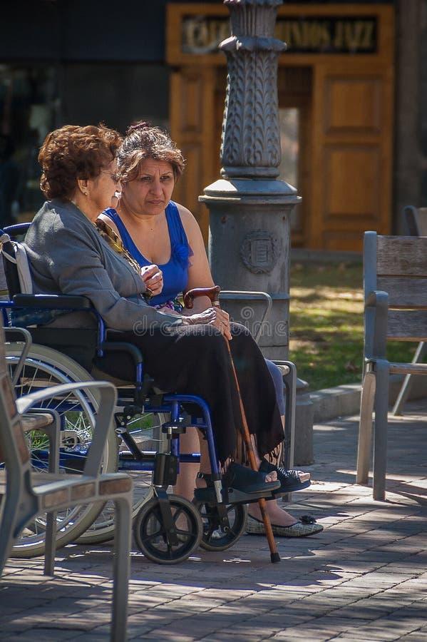一名女移民在一好日子照看一个轮椅的一名年长妇女在巴里阿多里德,西班牙,在2011年9月 库存照片
