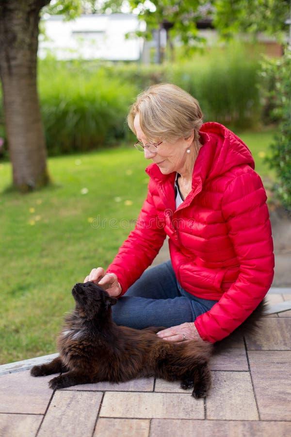 一名好年长妇女热情地抚摸她的猫 免版税库存图片