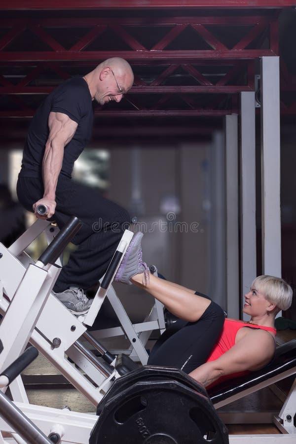 一名妇女和一个人腿的按在互相微笑的健身俱乐部度过美好时光和 库存照片