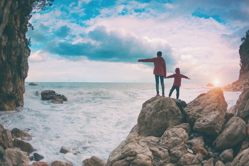 一名妇女和一个孩子的剪影反对海和天空 库存图片