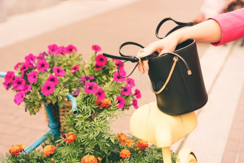 一名妇女在时装举行在手上一个黑提包 ?? 图库摄影