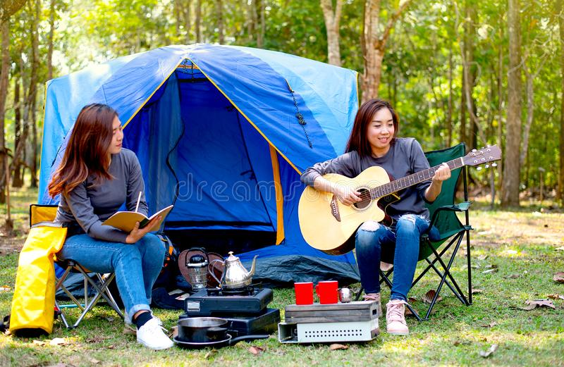 一名妇女弹吉他,当人一个记录某事在野营期间在森林里和神色时,如他们感觉乐趣和愉快 免版税库存图片