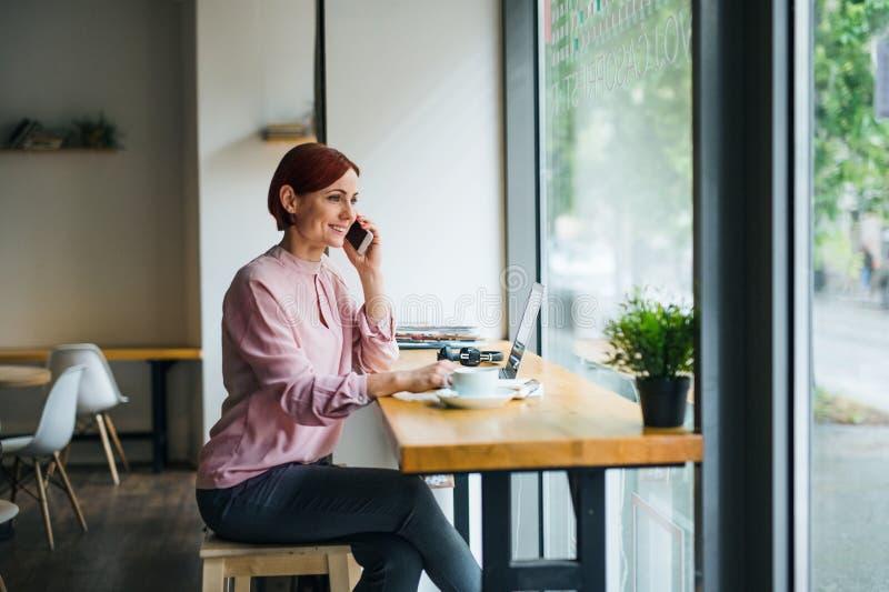 一名妇女用坐在咖啡馆的桌上的咖啡和电话,打电话 库存照片