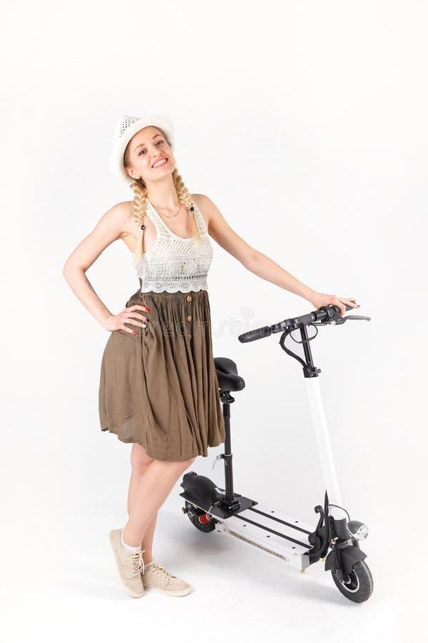 一名妇女的全长画象有在白色背景隔绝的白色滑行车的 免版税库存照片