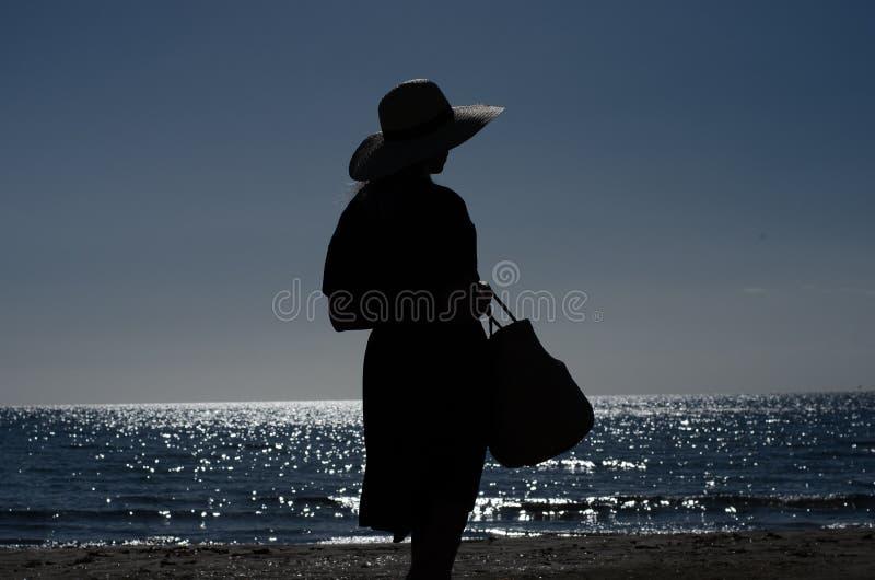 一名妇女的剪影有草帽的 库存照片