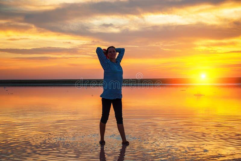 一名妇女的剪影水的在日落,与云彩的美丽的日落天空,旅游业概念 免版税库存图片