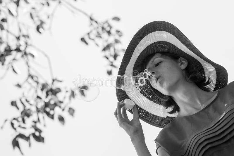 一名妇女的单色图象有帽子吹的泡影的 免版税库存照片