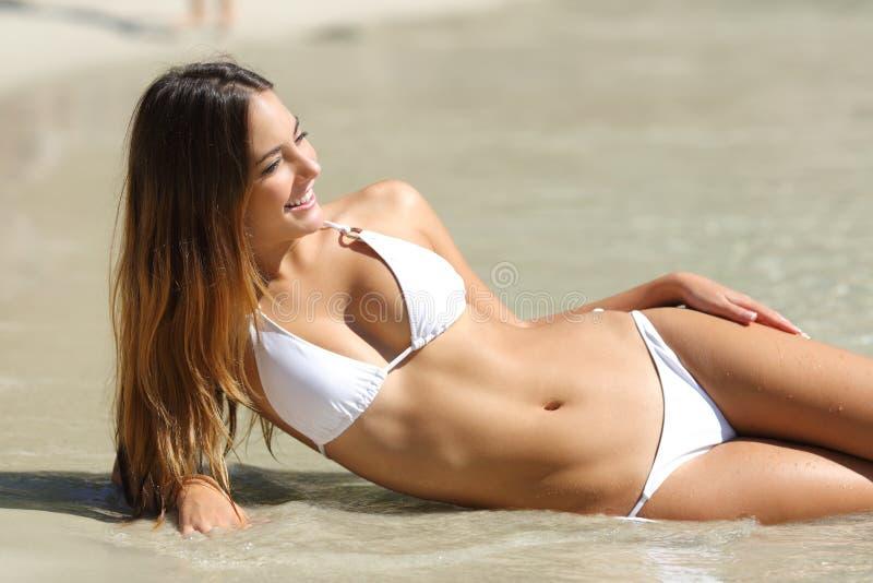一名妇女的完善的身体说谎在海滩的比基尼泳装的 免版税库存图片