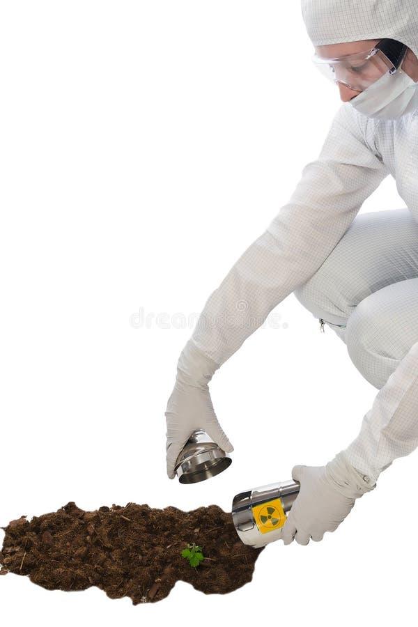 一名妇女的手橡胶手套的在地面由辐射沾染的容器收集,隔绝在白色 库存图片
