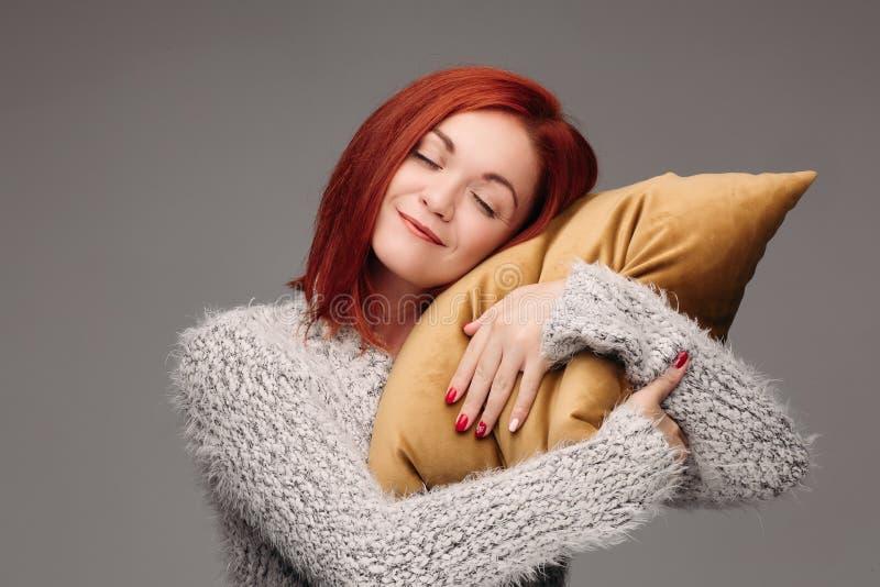 一名妇女的演播室画象拥抱枕头的毛线衣的 库存照片