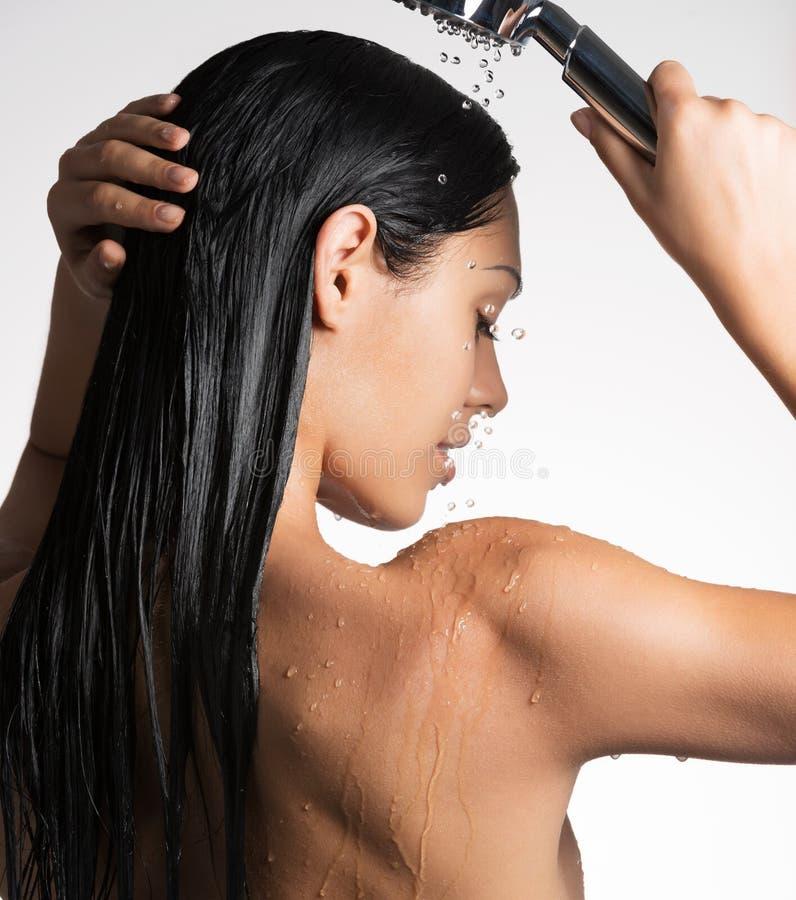 一名妇女的照片洗长的头发的阵雨的 库存图片