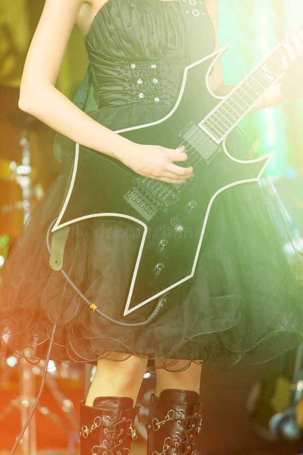 一名妇女的特写镜头使用在电镀吉他的阶段的 女孩rockstar在一件黑礼服 免版税库存照片