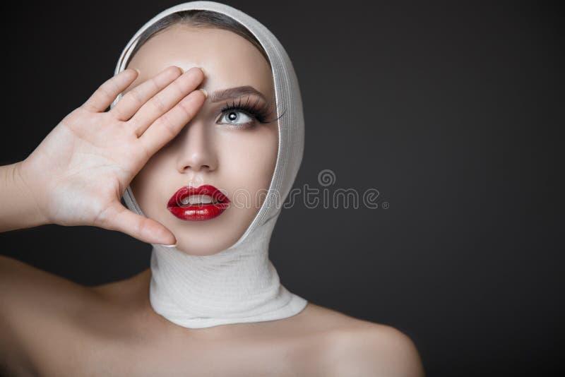 一名妇女的画象有明亮的构成的 长的睫毛和红色光滑的嘴唇 面孔构成 免版税库存照片
