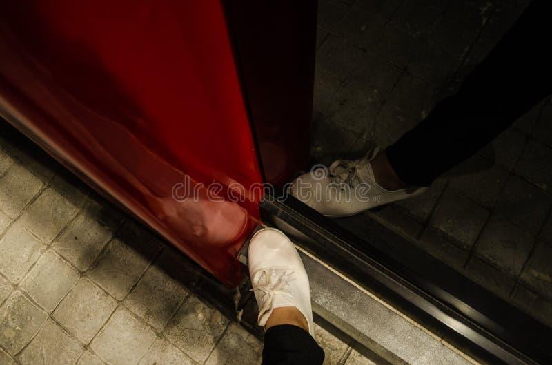 一名妇女的脚有白色鞋子的从上面看与反射她自己在有一个红色结构的一个黑镜子 免版税库存照片