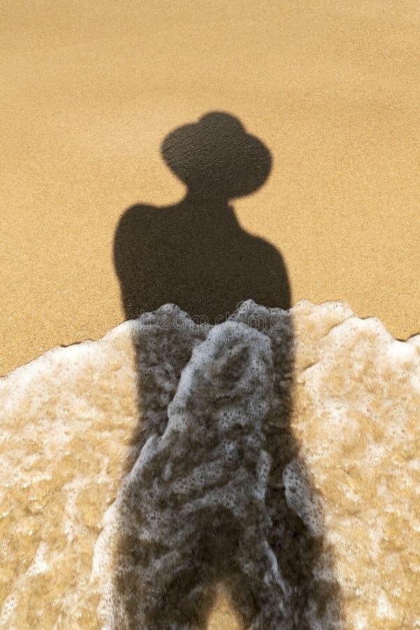 一名妇女的阴影由海的 免版税库存图片