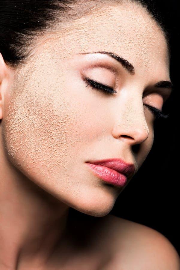 一名妇女的面孔有化妆粉末的在皮肤 图库摄影