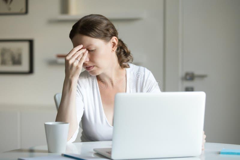 一名妇女的画象书桌的有膝上型计算机的,在前额的手 库存图片