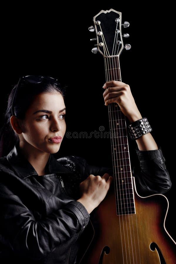 一名妇女的画象皮夹克的有声学吉他的 图库摄影