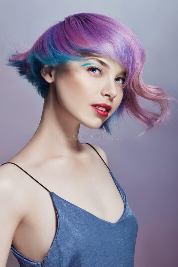 一名妇女,紫色所有树荫的画象有明亮的色的飞行的头发的  头发染色、美丽的嘴唇和构成 头发 免版税库存照片