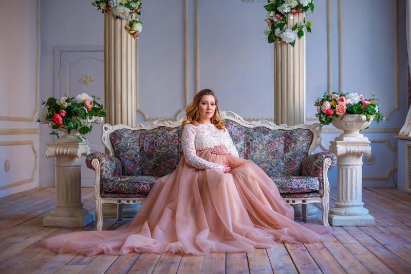 一名孕妇在一件美丽的礼服坐长沙发 母性的概念 免版税图库摄影