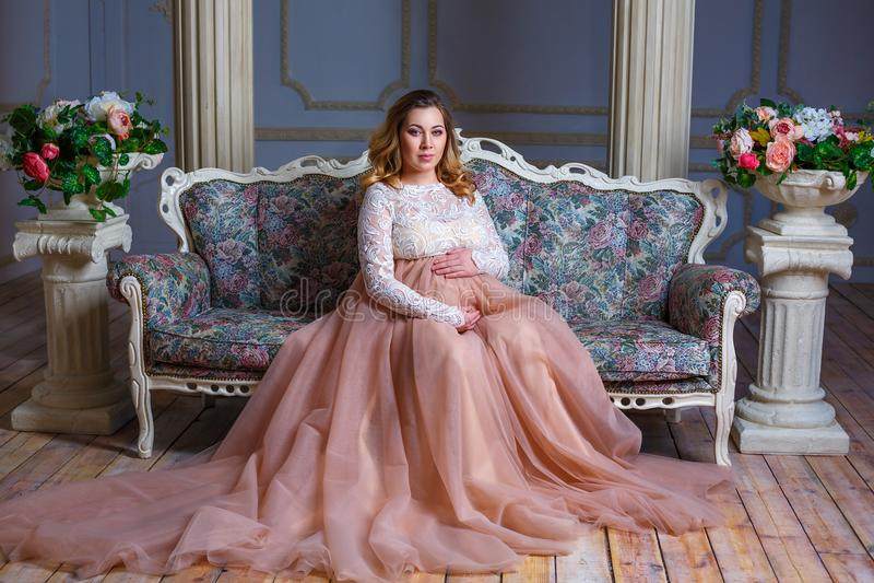 一名孕妇在一件美丽的礼服坐长沙发 母性的概念 免版税库存照片